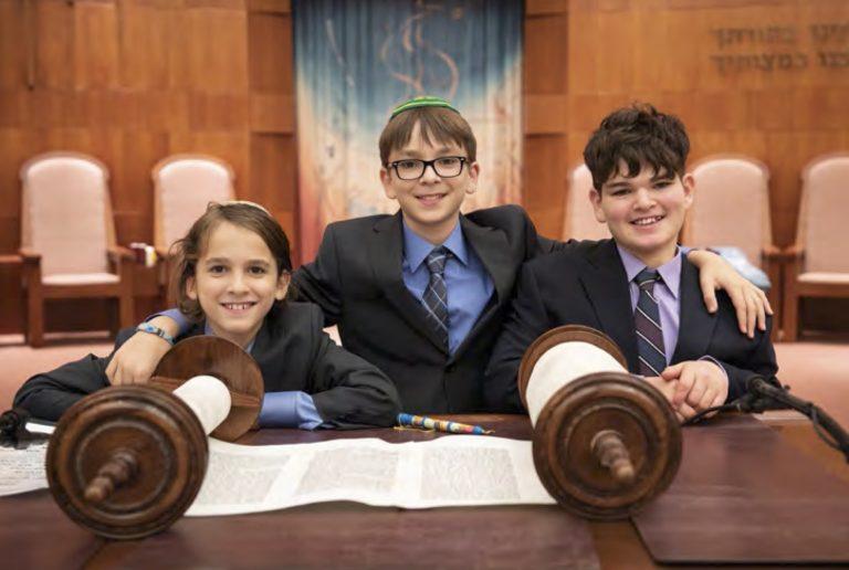 three kids standing in front of Torah