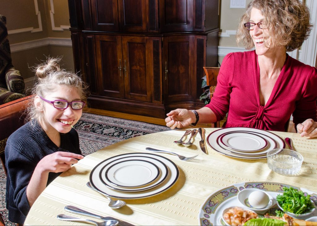 photo of a parent and child smiling at the Seder table