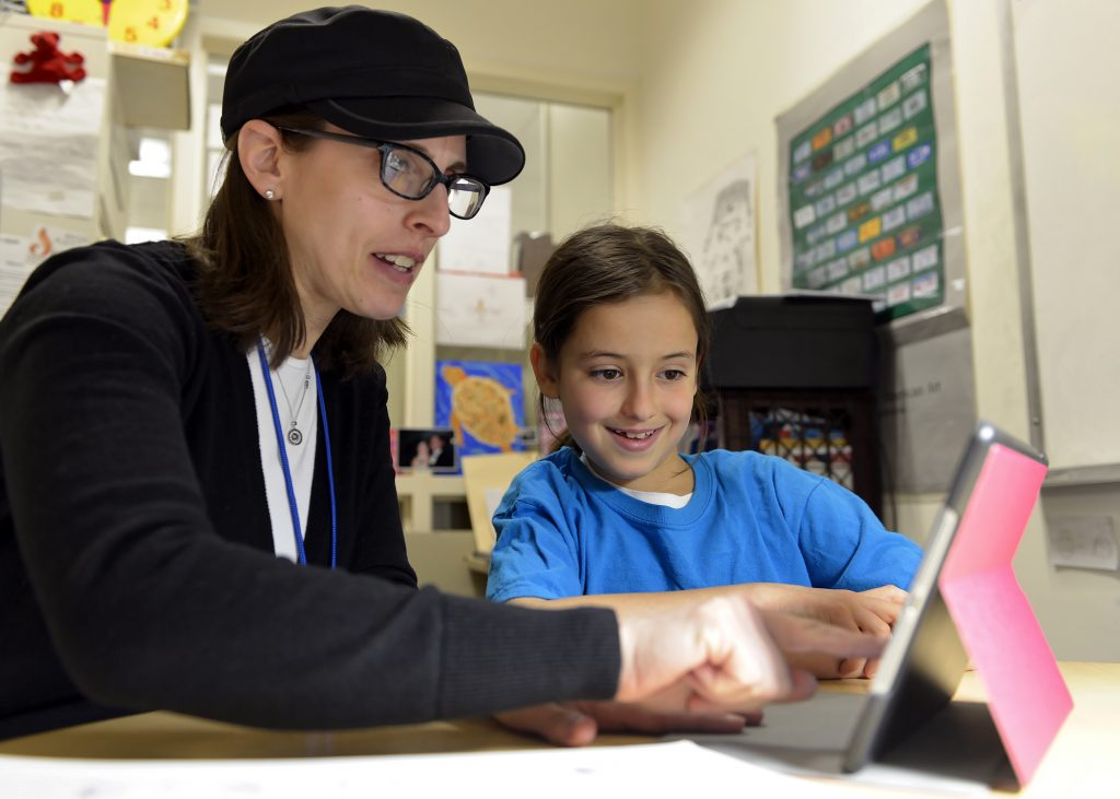 photo of a teacher working with a student