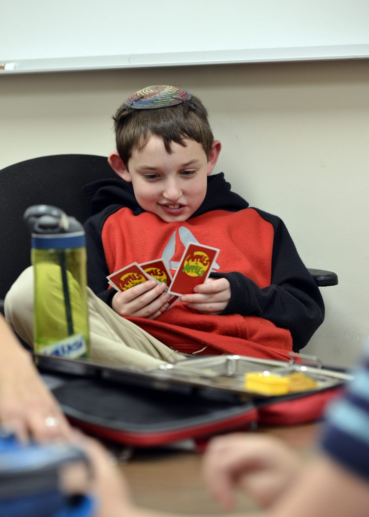 photo of a day school student playing cards