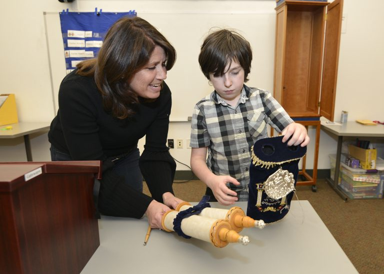 Boy unwrapping Torah with teacher