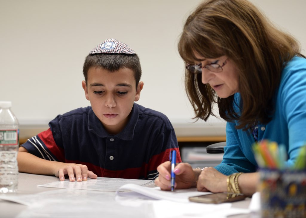 photo of a day school therapist working with a student writing something