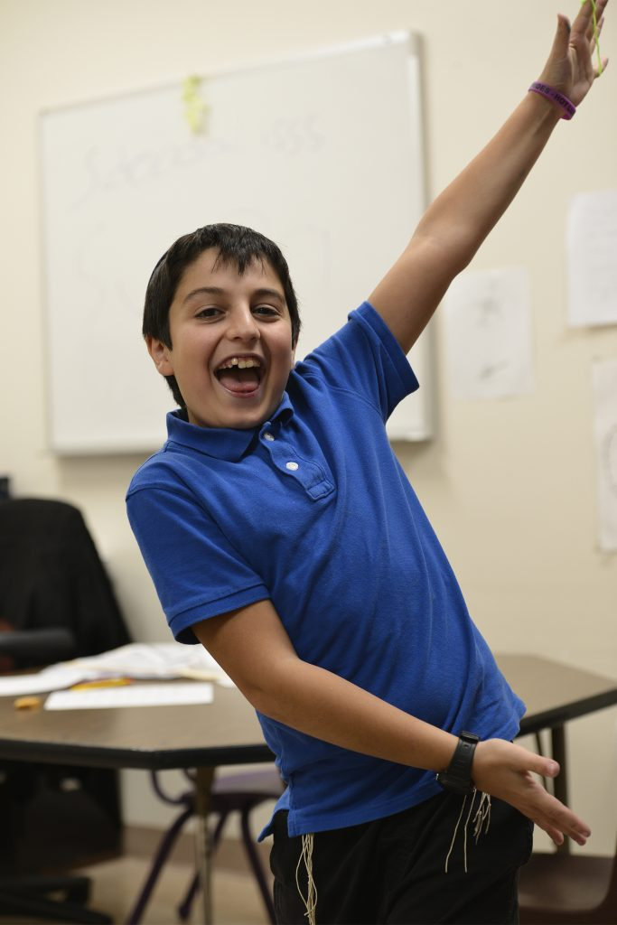 photo of a day school student, standing, smiling, with his arms up