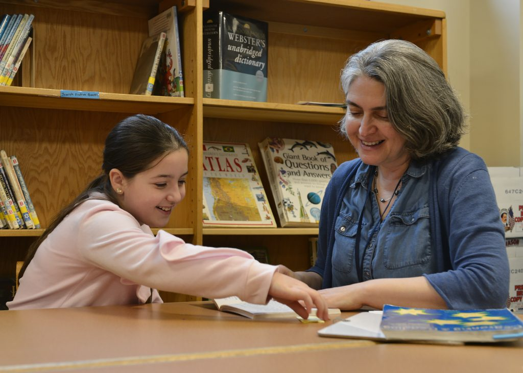 photo of a day school therapist reading with a student
