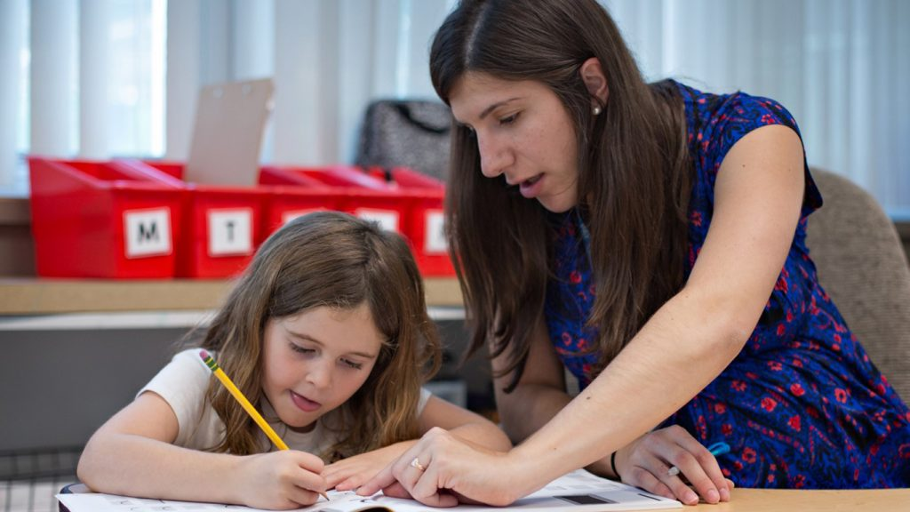 photo of a day school educator helping a student