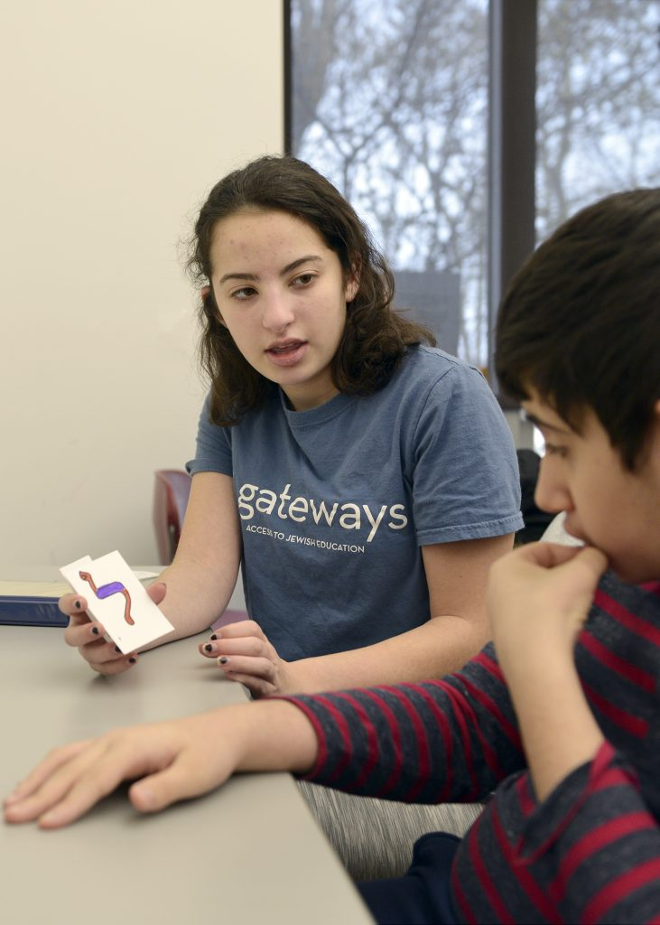 volunteer showing student a Hebrew letter flashcard