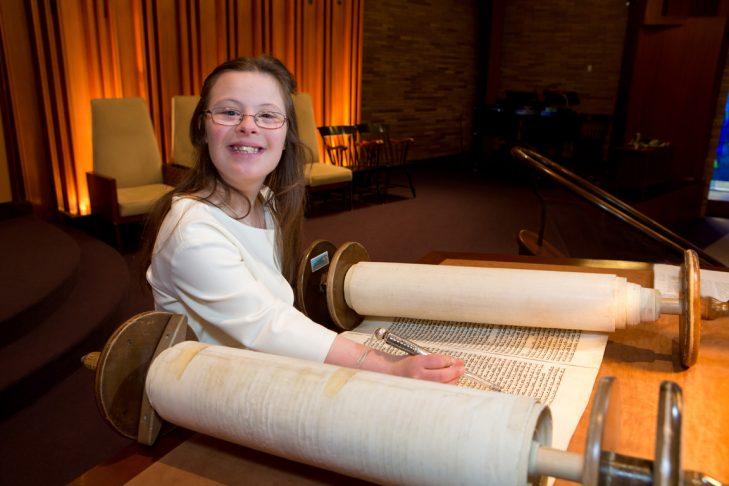 girl smiling while reading Torah