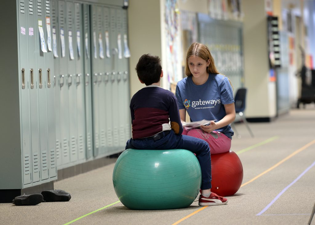 student and teen volunteer sitting on exercise balls