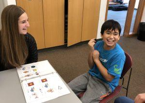 student and volunteer smiling looking at binder