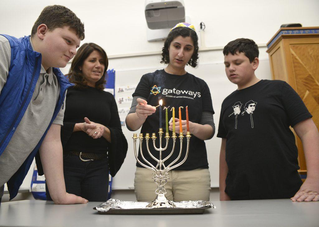 four people lighting a hanukkiah