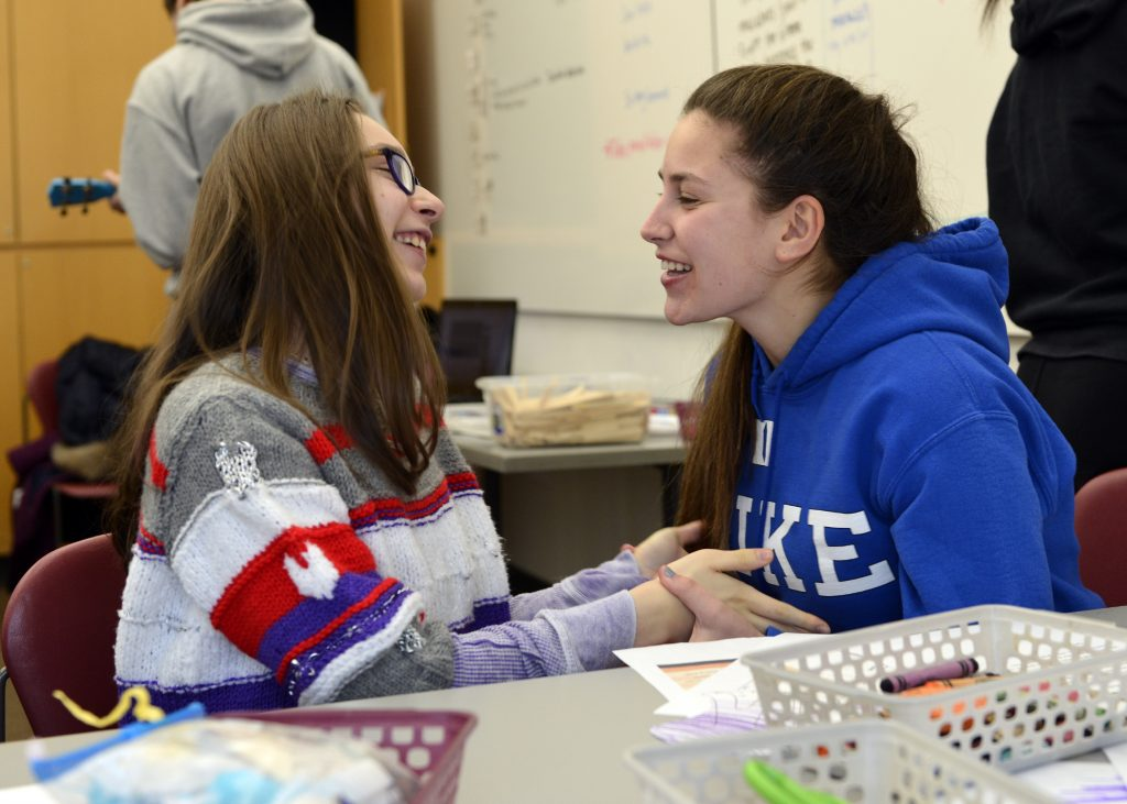 photo of a teen volunteer and student facing each other smiling and holding hands
