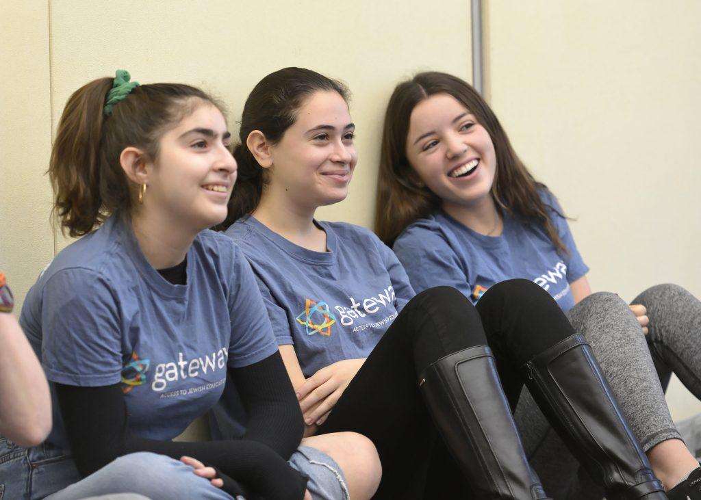 Three teen volunteers smiling