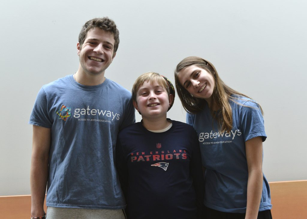 photo of two teen volunteers smiling with a student