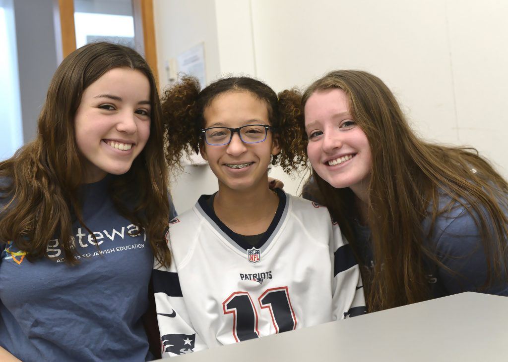 two volunteers and a student smiling