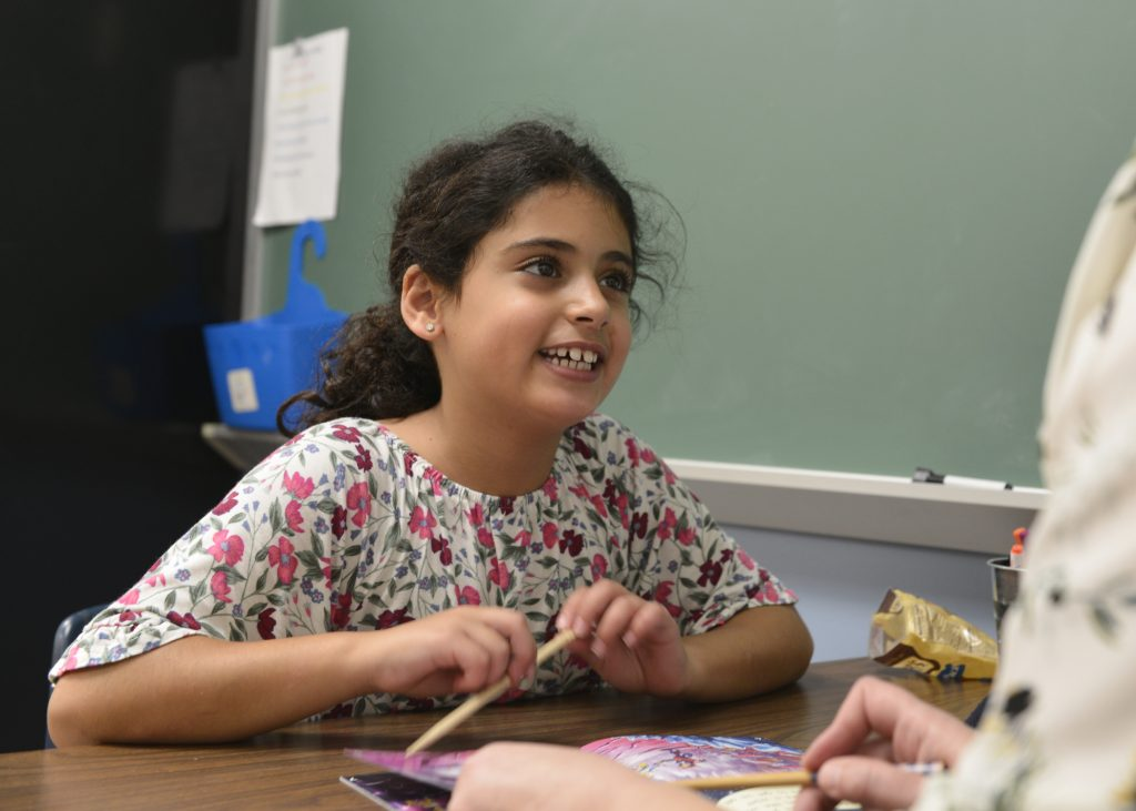 girl smiling holding a pencil