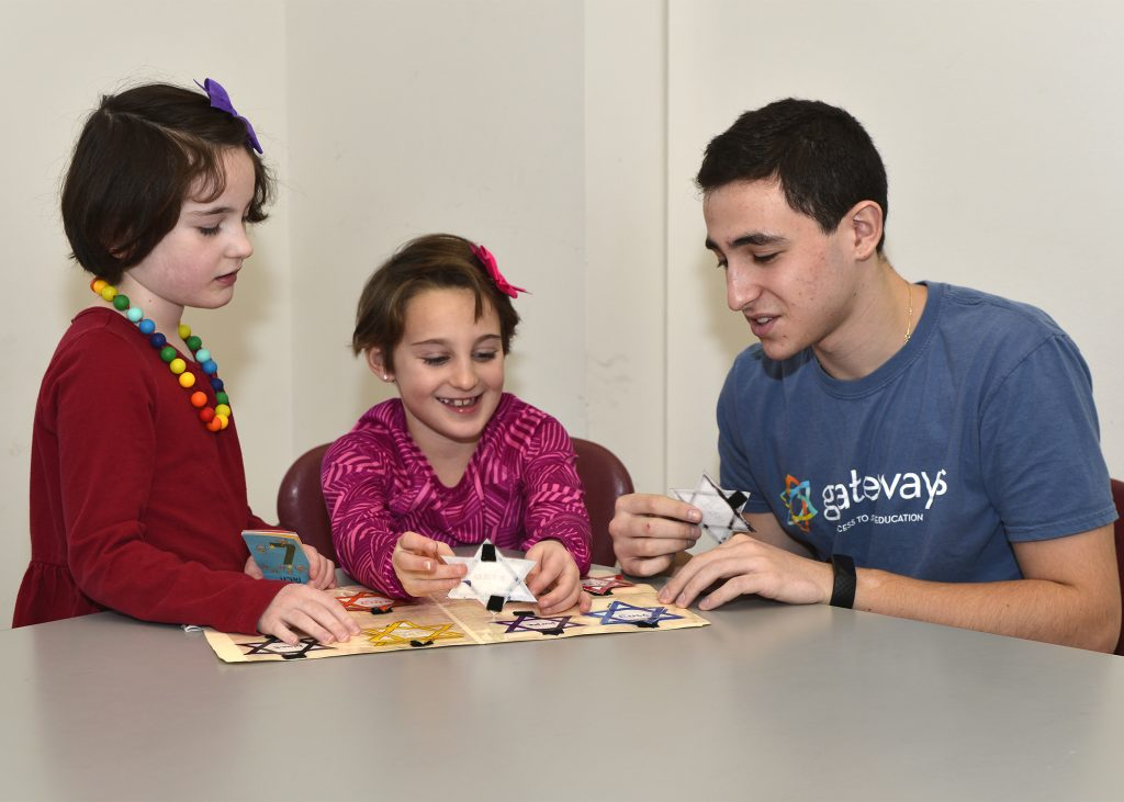 teen volunteer playing a game with two students