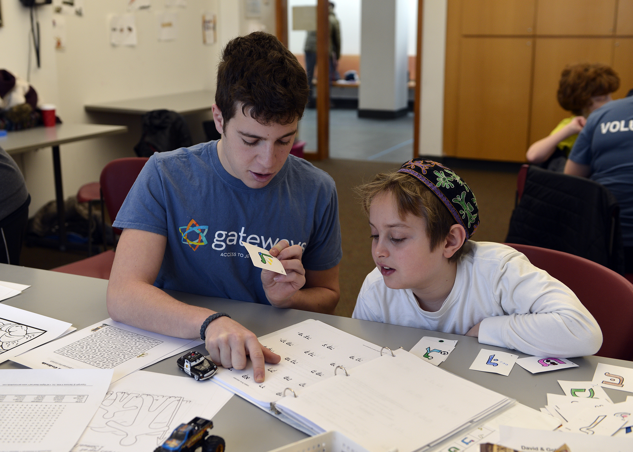 student and volunteer learning Hebrew