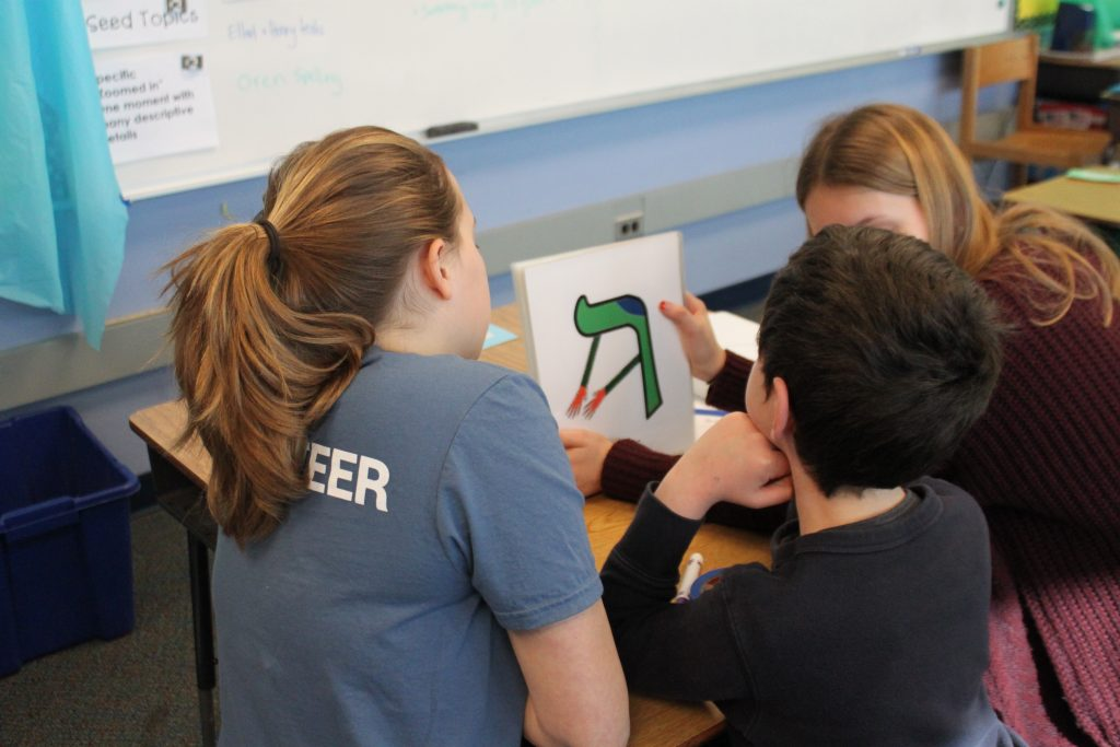 student and volunteers looking at Hebrew letter resh
