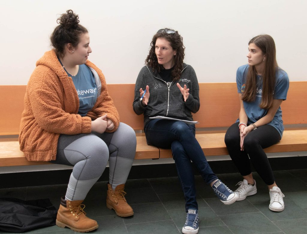 two teen volunteers talking to a teacher
