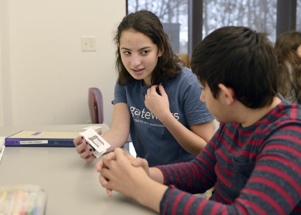 student and volunteer practicing Hebrew