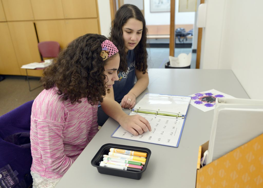 photo of a volunteer helping a student with Hebrew