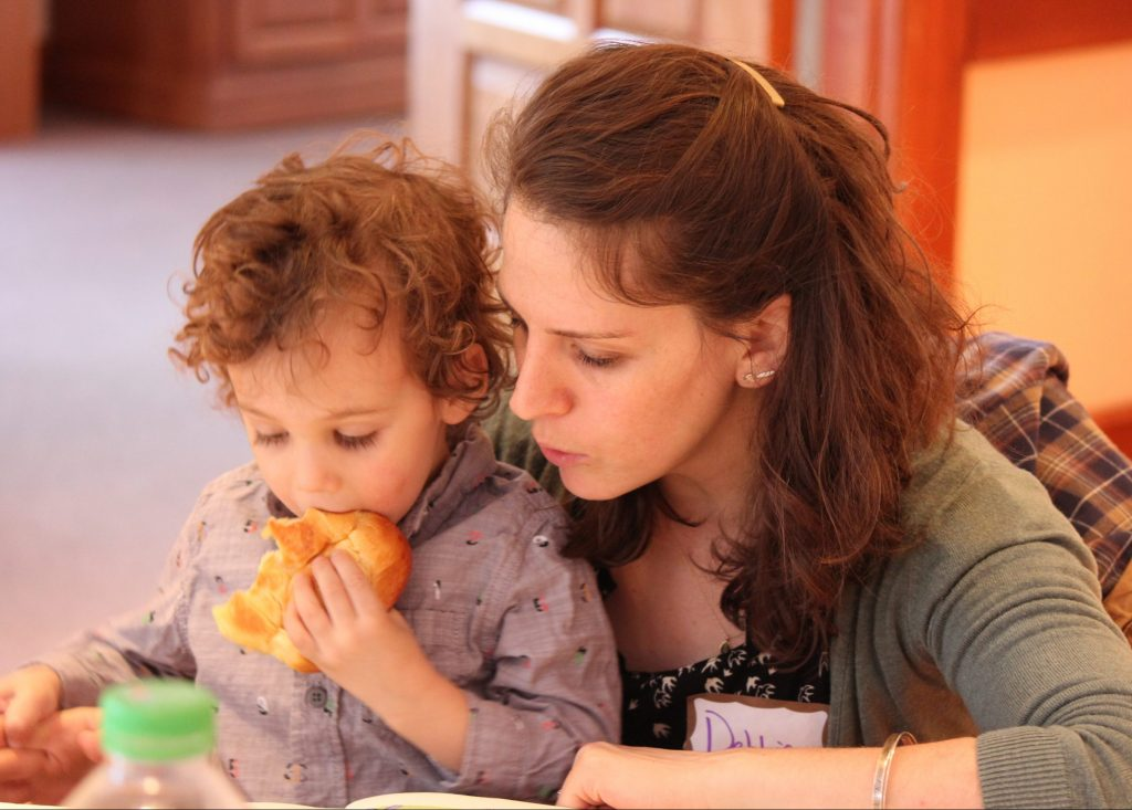 photo of a parent and child saying Shabbat blessings, child is eating challah