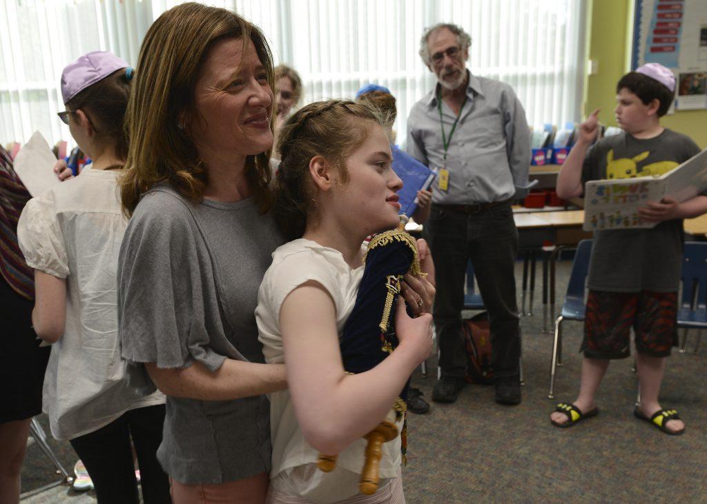 photo of a B'nei Mitzvah student and parent carrying a torah