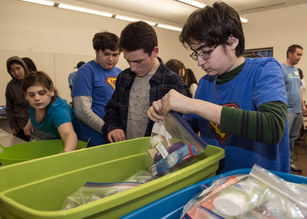 photo of Mitzvah Mensches students stuffing care packages