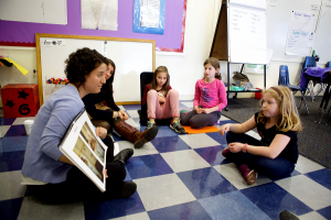 photo of a teacher reading a book to three students