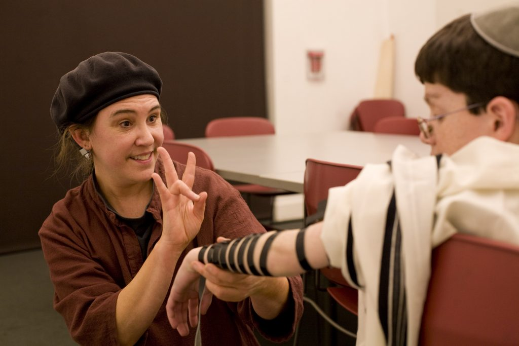 photo of Gateways tutor showing a b'nei mitzvah student how to put on tefillin