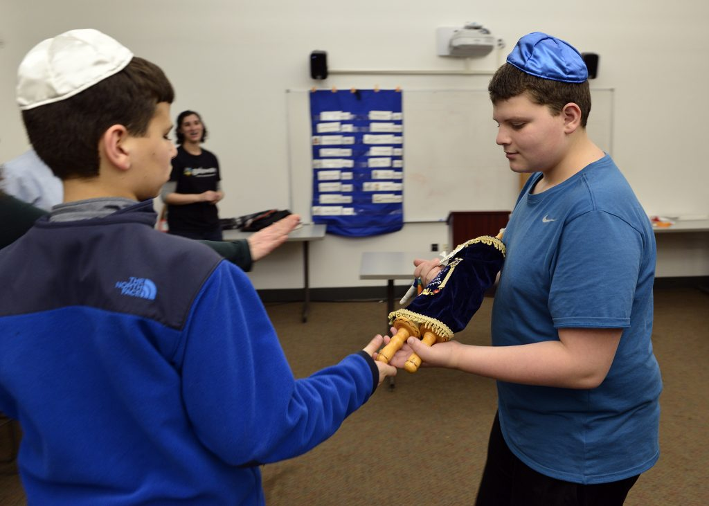 photo of two students passing a Torah