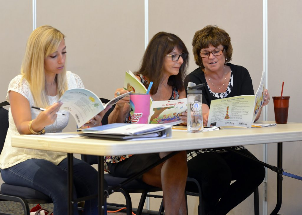 photo of three educators reading at a workshop