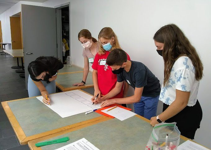 photo of group of teen volunteers working on a poster