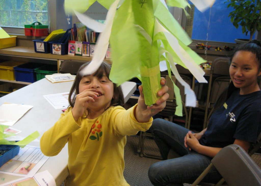 photo of a student smiling and shaking a pretend lulav