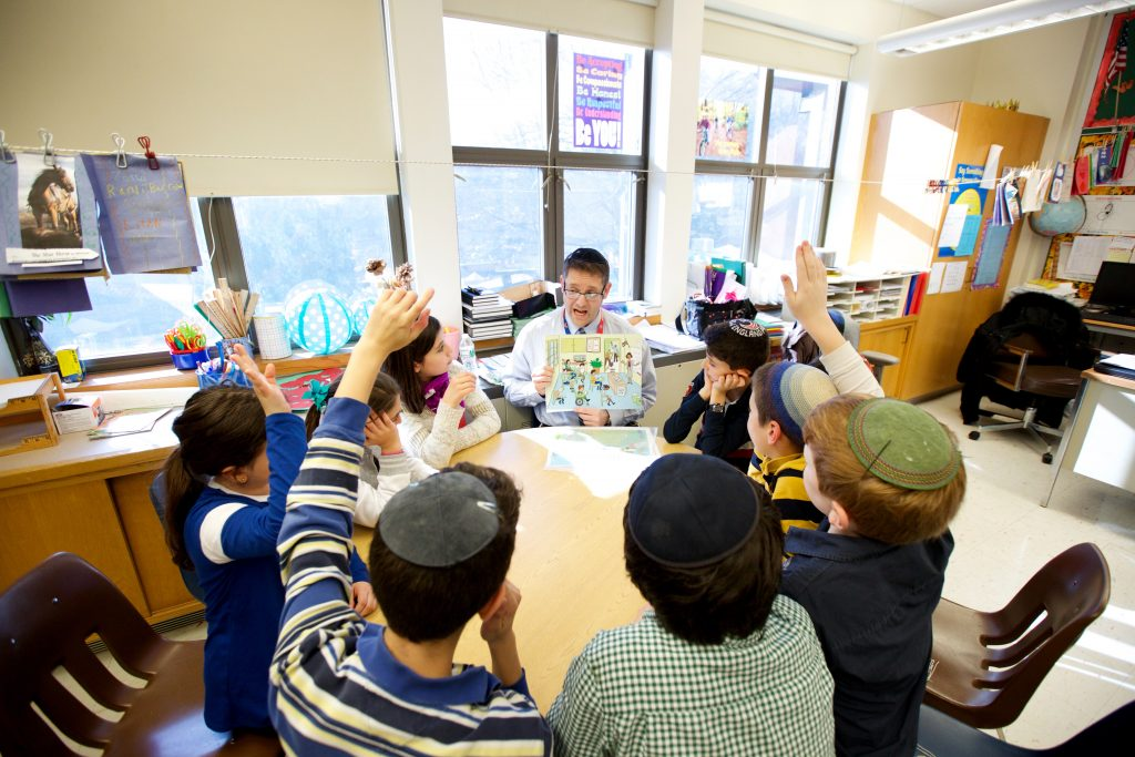 photo of a teacher reading a book to a group of students