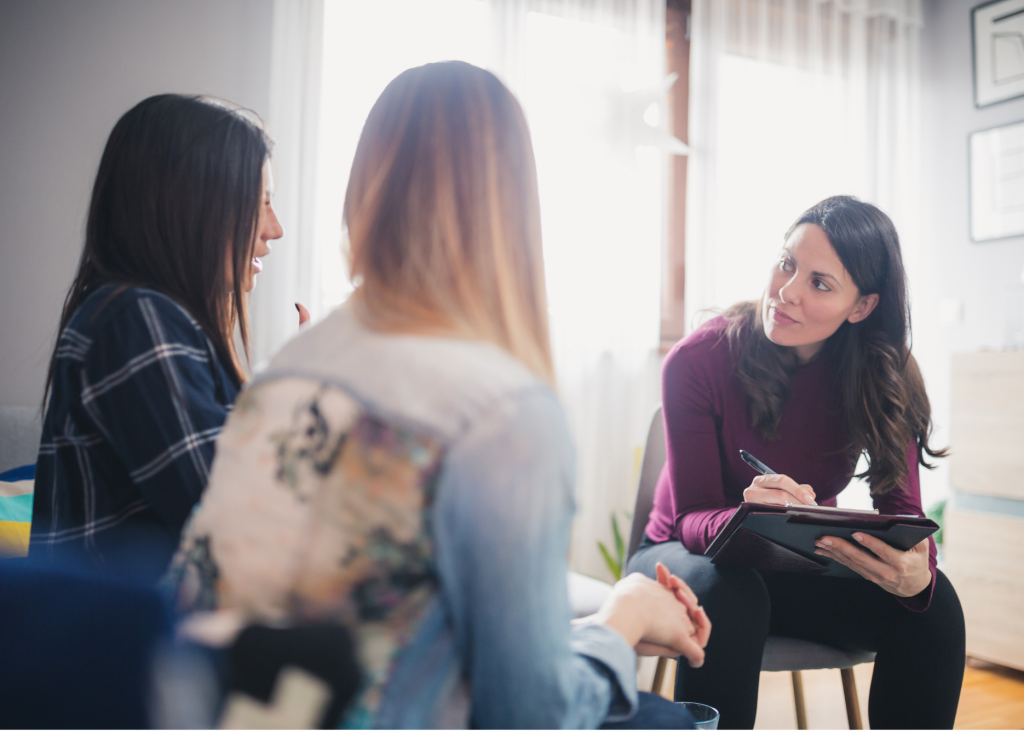 photo of a counselor sitting and talking to two girls